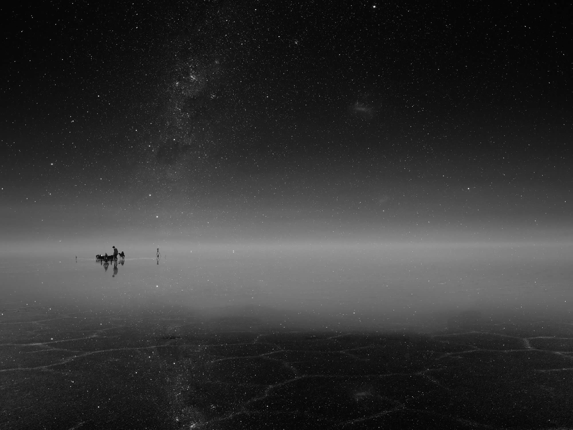 The stars are reflected in the water on the salt flat